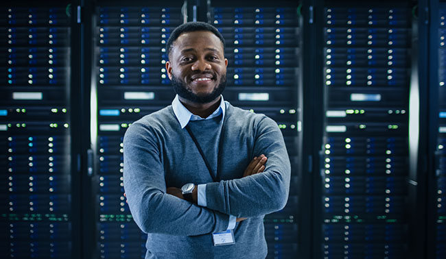 Bearded Black It Engineer Standing And Posing With Crossed Arms In The Middle Of A Working Data Center Server Room With Server Computers Working On A Rack