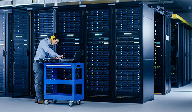 In Data Center It Engineer Wearing Protective Muffs Installs New Hardware For Server Rack Specialist Doing Maintenance Running Diagnostics And Updating Hardware For Stable Functioning Of A System