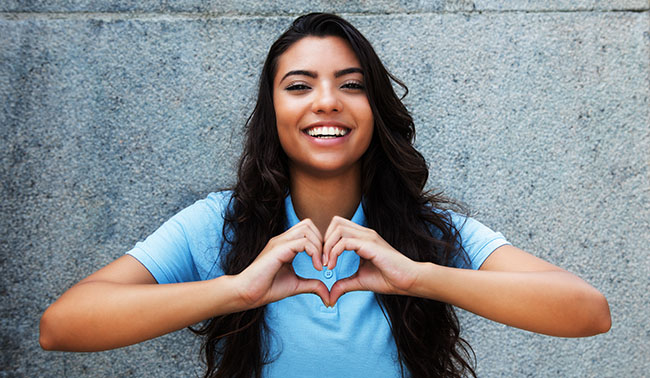 Laughing Latin American Woman In Love Showing Heart With Hands