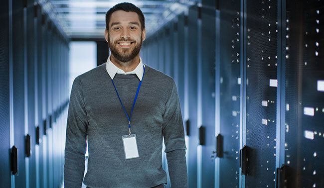 Portrait Of An It Engineer He Smiles And Folds His Arms On A Chest He 039 S Working In Data Center Full Of Rack Servers
