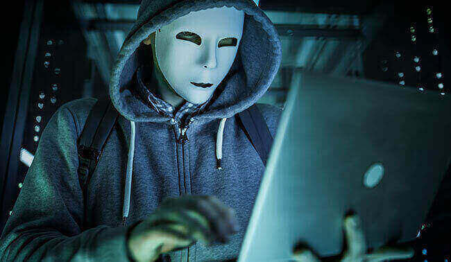 Close Up Shot Of A Masked Hacker In A Hoodie Standing In The Middle Of Data Center Full Of Rack Servers And Hacking It With His Laptop