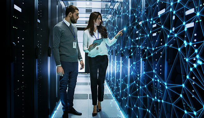 Female And Male It Engineers Discussing Technical Details In A Working Data Center Server Room With Internet Connection Visualization