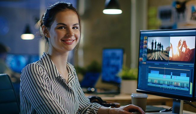 Female Video Editor Turns And Warmly Smiles Into The Camera Her Office Is Modern And Creative Loft Studio