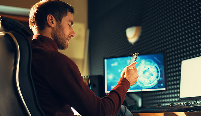 Young Man Working In The Studio Using A Smartphone And Computer